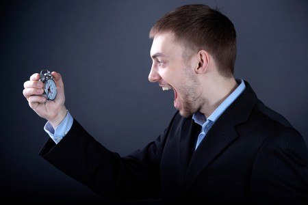 dissatisfaction: Portrait of young man looking at clock and shouting Stock Photo