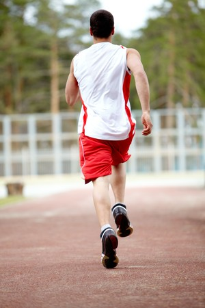 back ground: Rear view of energetic sportsman running down stadium track