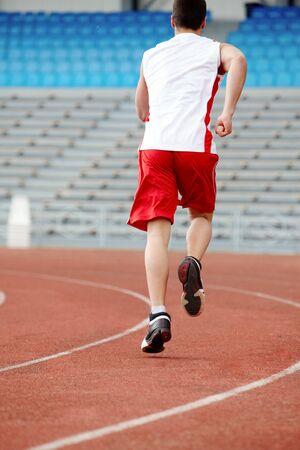 Back of guy in sportswear running down stadium track photo