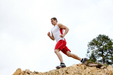 Image of healthy athlete running down cliff  photo