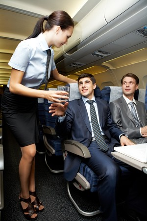 Image of pretty stewardess giving glass to businessman in airplane Stock Photo - 6894581
