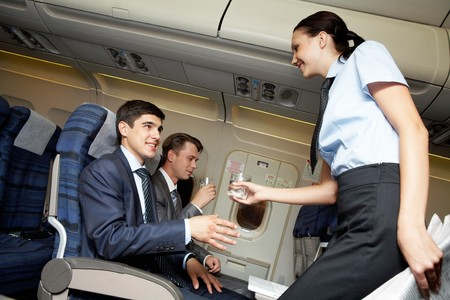 corporate airplane: woman holding and giving glass of water to young businessman  Stock Photo