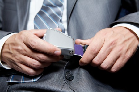 passenger plane: Close-up of businessman fastening security belt in airplane Stock Photo