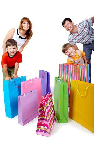 ni�os de compras: Imagen de miembros de la familia alegres cerca de coloridos bolsas de compra, mirando la c�mara