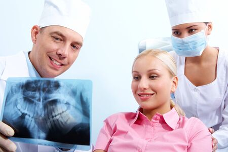 Portrait of woman with dentist showing her x-ray behind assistant   photo