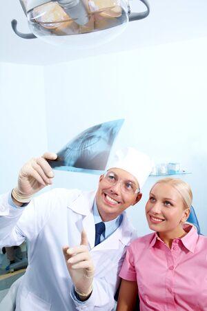 Image of dentist showing x-ray to patient at medical examination photo