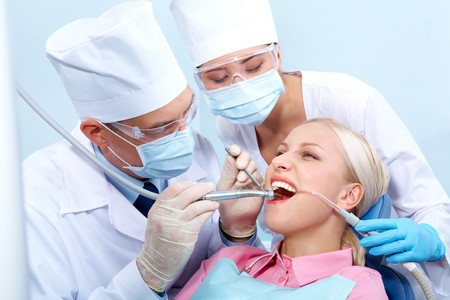 Image of dentist treating woman's teeth and assistant near by Stock Photo - 6894816