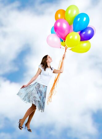 Pretty young woman flying on colorful balloons in the sky photo