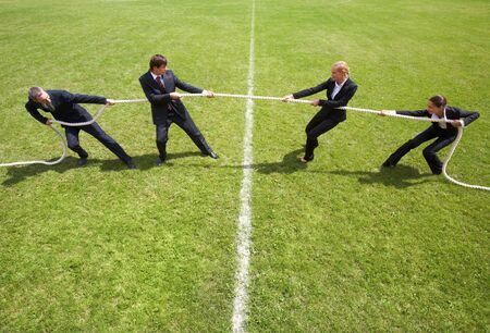 warfare: Businessmen and businesswomen playing tug of war Stock Photo