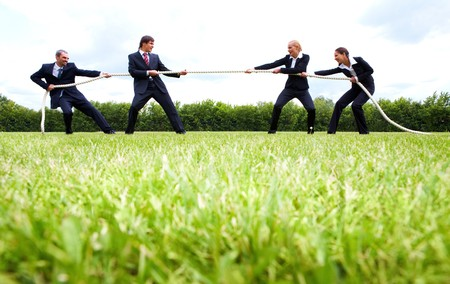 tug of war: business people stretching the rope in the stadium  Stock Photo