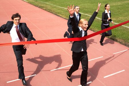 running businessman: happy businesswoman crossing finish line during race  Stock Photo