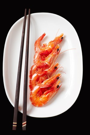 Image of tasty shrimps lying in row with two chopsticks near by photo