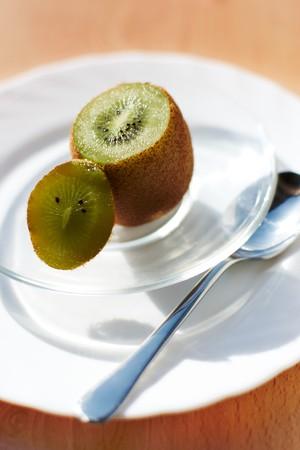 Image of fresh kiwi cut in glassy vase photo