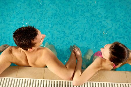 Above view of happy man and pretty girl in swimming pool photo