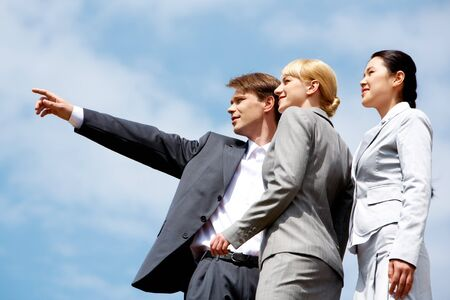 company profile: Close-up of businessman pointing at something while two elegant ladies looking at it Stock Photo