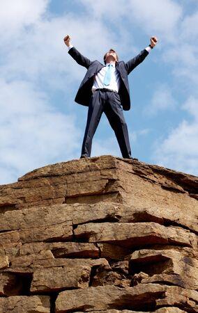 Happy businessman standing on the top of mount with his arms raised to the sky  Stock Photo - 6962896