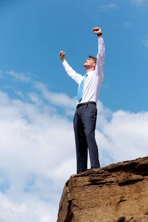 Serena empresario de pie en la cima de un monte con sus brazos alzados al cielo  Foto de archivo