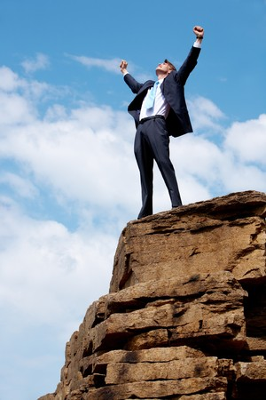 Photo of joyful businessman raising his arms upwards while standing on the rocky cliff photo
