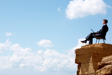 employees working: Portrait of businessman sitting on the chair on edge of cliff