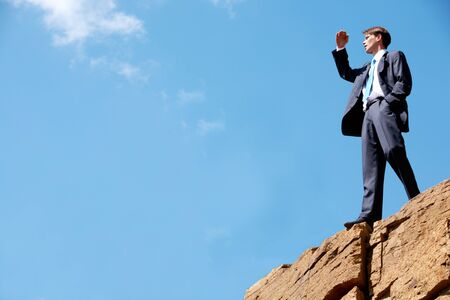 looking into: Photo of happy businessman standing on the cliff and looking into the distance on the background of bright sky