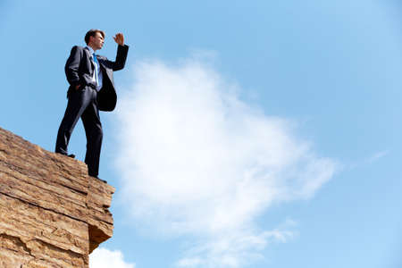 Photo of happy businessman standing on the cliff and looking into the distance on the background of blue sky photo