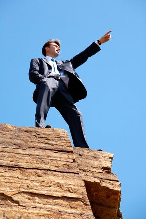 Photo of serious businessman standing on the cliff and pointing into the distance on the background of blue sky photo