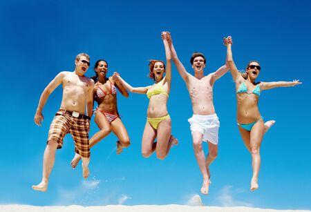 Joyful team of friends jumping on sandy beach and shouting