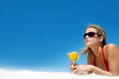 sexy beach girl: Portrait of charming woman with orange cocktail and sunglasses on the background of sky