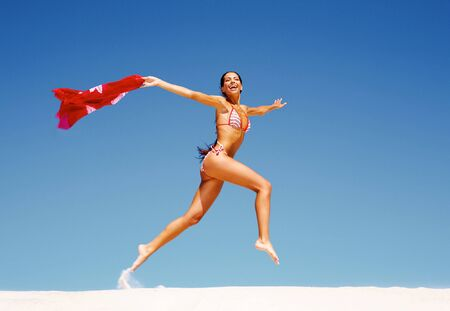 Image of happy girl running down sandy beach in summer photo