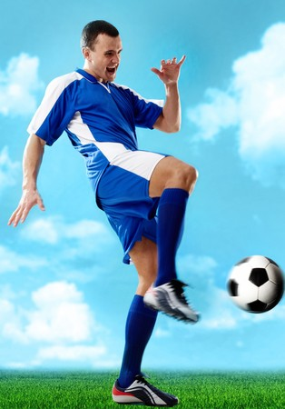 Portrait of soccer player hitting the ball