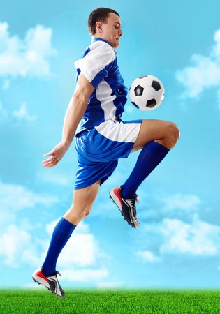 Portrait of soccer player jumping with ball on a blue background  photo