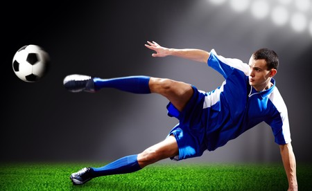 kicking ball: Image of soccer player doing flying kick with ball on football field