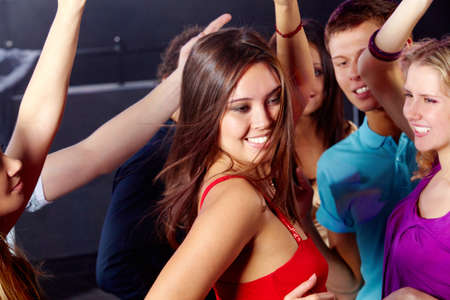 Image of pretty girl dancing on background of clubbing friends photo