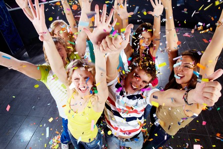 Photo of excited teenagers in confetti raising their arms expressing joy Stock Photo - 6963256