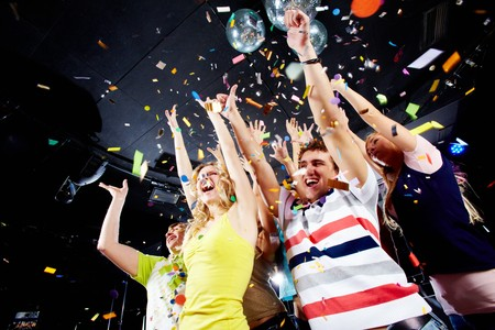 people partying: Photo of excited teenagers in confetti raising their arms expressing joy