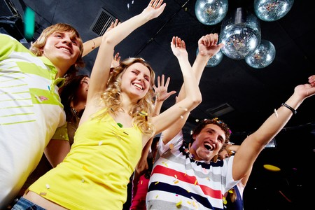 Photo of excited teenagers raising their arms in joy photo