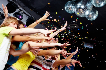 people partying: Photo of emotional teenagers stretching arms forwards in excitement