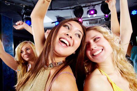 Two joyful girls dancing in night club and having fun photo