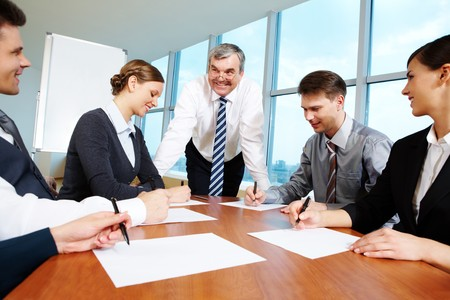 Smart and confident boss looking at managers writing on papers at meeting photo