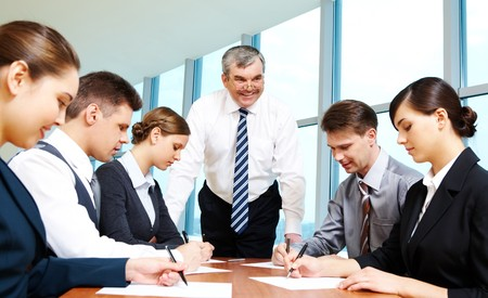 Smart and confident boss looking at managers with papers at meeting photo