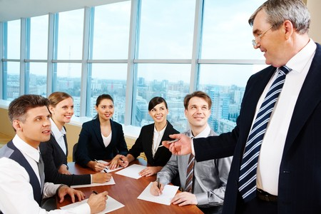 Smart and confident boss looking at managers with papers at meeting