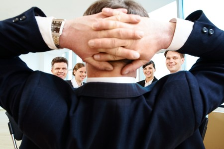 Rear view of aged businessman with his hands behind head looking at happy partners Stock Photo - 6963008