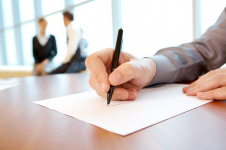 executive courses: Close-up of male hand with pen over paper during conference Stock Photo