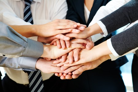 collaboration: Image of business partners hands on top of each other symbolizing companionship and unity