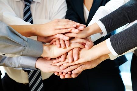 manos unidas: Imagen de asociados de negocios de manos en la parte superior de cada uno a otro que simboliza el compa�erismo y la unidad