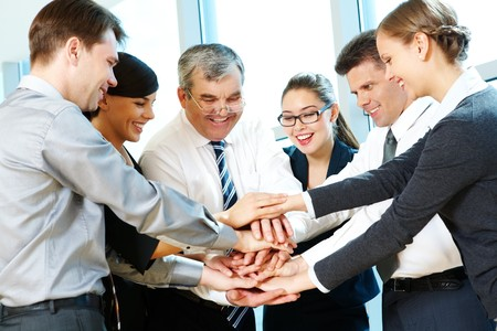 joining together: Photo of smiling co-workers making pile of hands and looking at camera