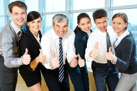 Portret van tevreden medewerkers kijken camera met een glimlach en teken van goed weer gegeven: