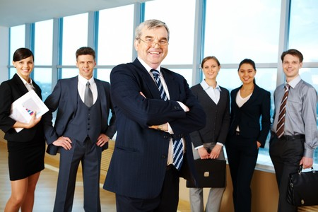 Image of senior leader smiling at camera with several employees behind Stock Photo - 6962929