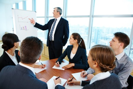 Smart and confident boss pointing at whiteboard while making presentation Stock Photo - 6963006