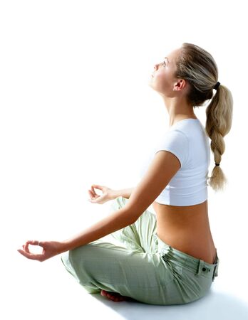 Attractive woman meditating in pose of lotus and looking at light photo